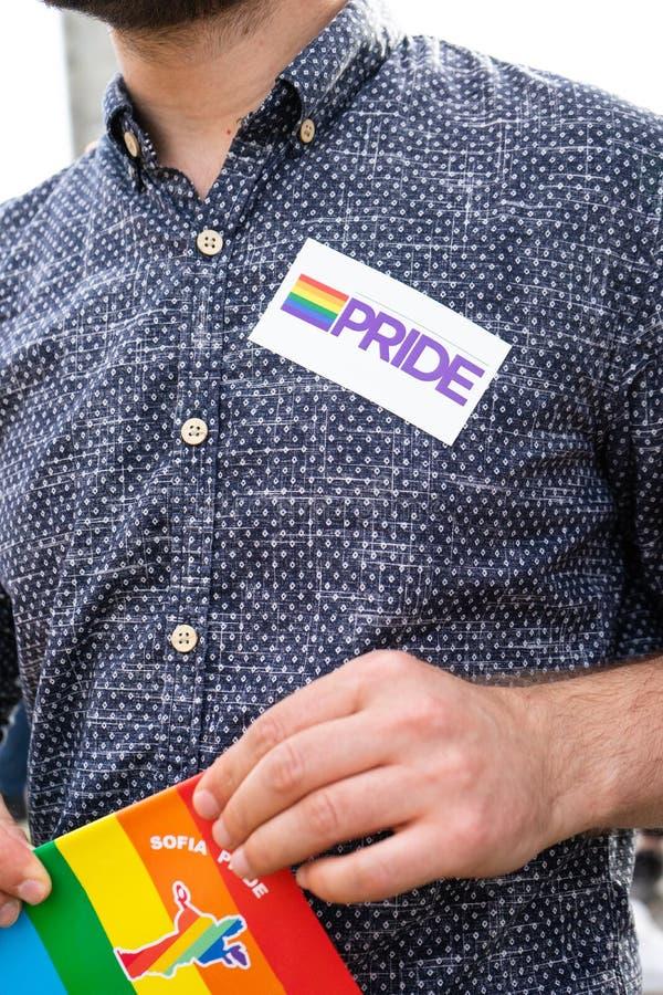 Gay in Sofia Pride March con l'autoadesivo in bandiera dell'arcobaleno e del petto in sua mano fotografia stock libera da diritti
