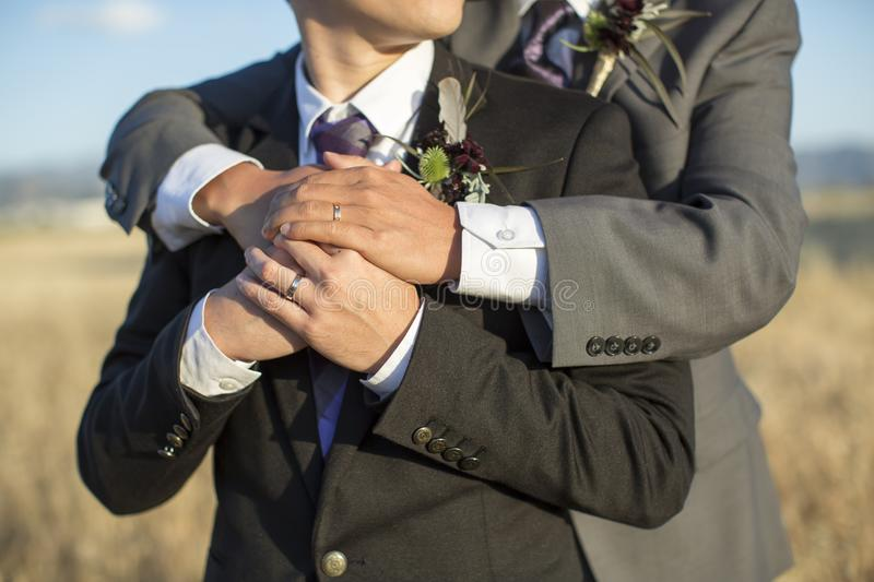 Gay wedding couple embracing outside royalty free stock photography