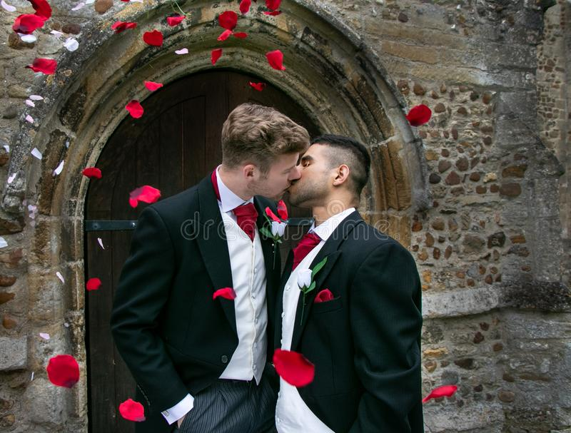 Gay wedding, grooms leave village church after being married to smiles and confetti royalty free stock image