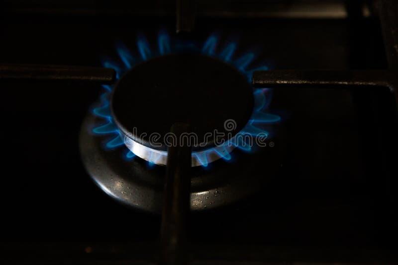 Gaz bleu brûlant sur le fourneau foncé Cuisinière à gaz de brûleur, concept d'énergie plan rapproché, foyer sélectif photo stock