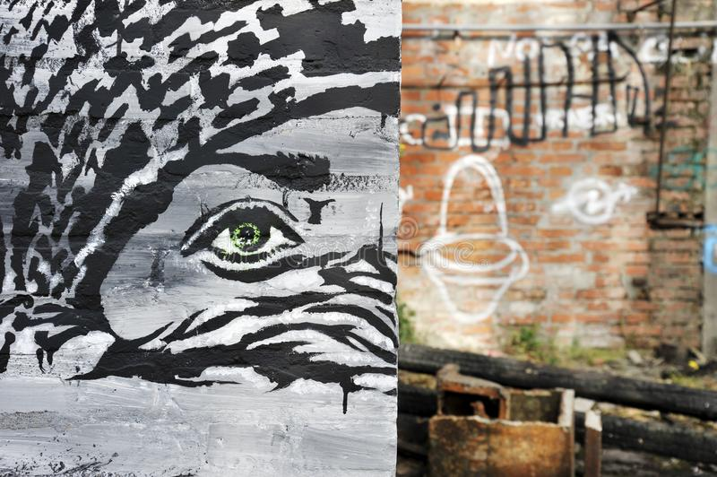The gaze of a girl from under a Kefiah in a street art mural. On the background the war rubble. War concept. Unknown artist. stock photography