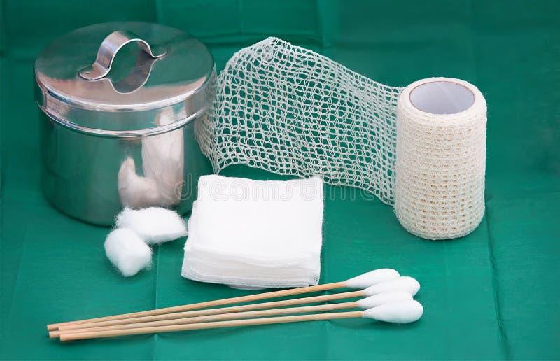 Gaze, pot inoxydable, bandage net de petit pain, écouvillon, ouate sur le vert photos stock