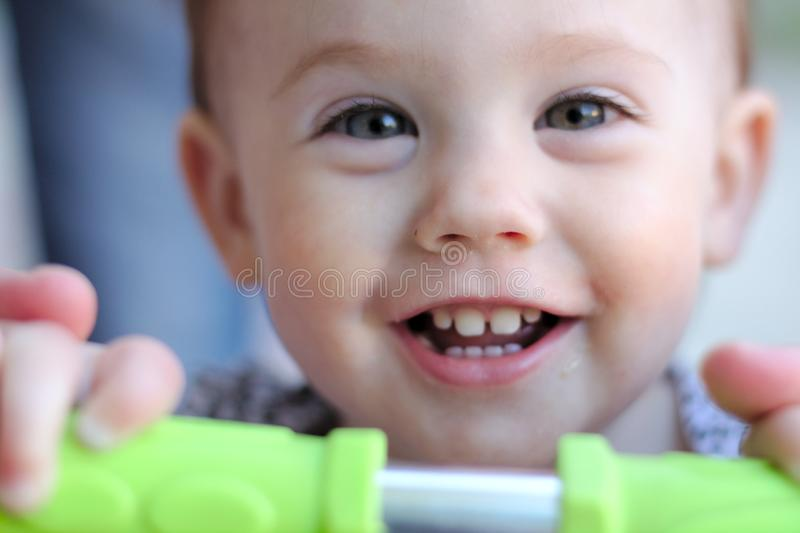 gaze of a smiling little child with blond hair holding onto the green handles of a scooter royalty free stock photos