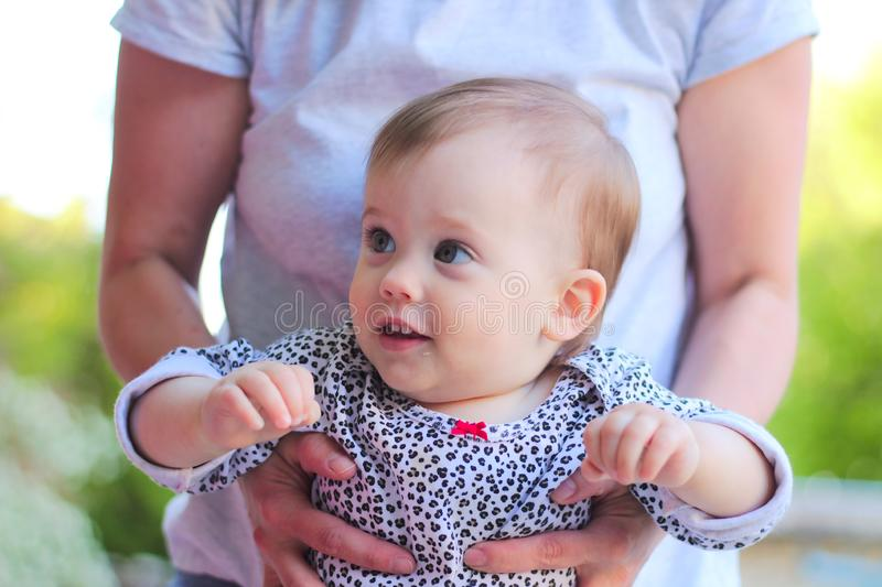 gaze of a smiling little child with blond hair in mom& x27;s hands stock photos