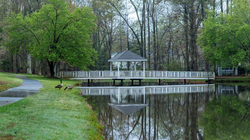 Gazebo on bridge going over pond royalty free stock photography