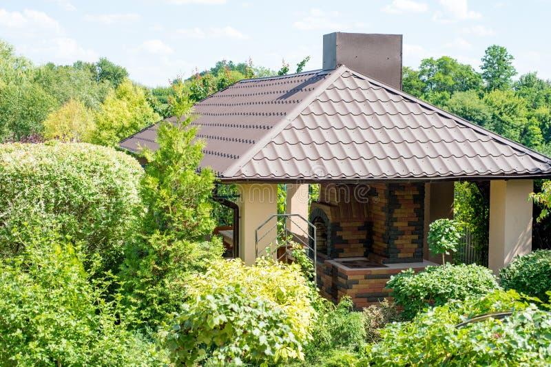 Gazebo con el lugar para la barbacoa en un jardín verde jugoso del verano fotos de archivo