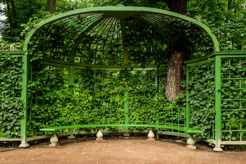 gazebo con il banco nel giardino di estate del parco, StPetersburg, Russia fotografie stock libere da diritti