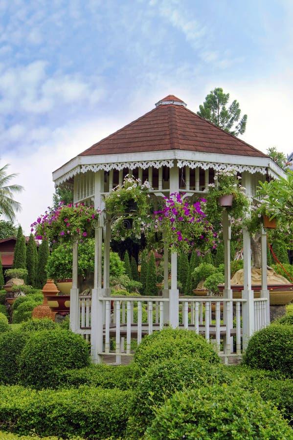 Gazebo de madera al aire libre con las flores en un jardín hermoso foto de archivo