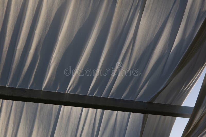 Gazebo de madera en la luz de oro de la hora, casi puesta del sol: cercano para arriba de los paños blancos, luz suave, humor del foto de archivo libre de regalías