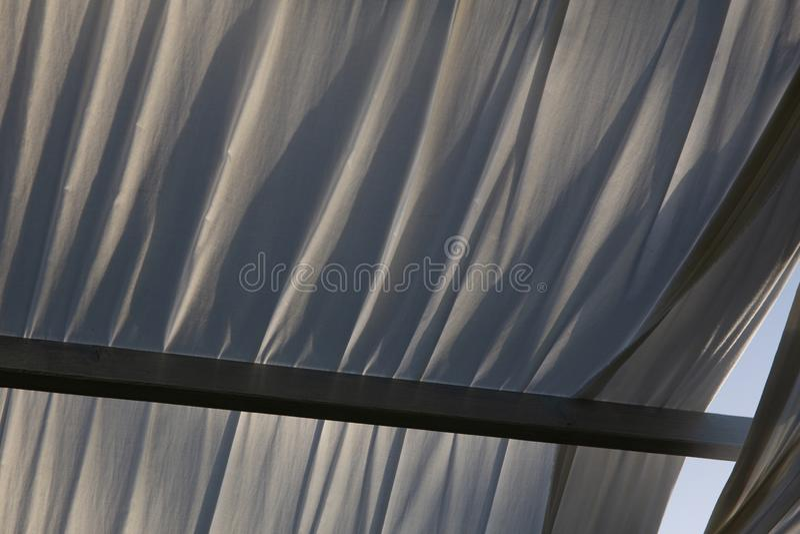 Gazebo de madera en la luz de oro de la hora, casi puesta del sol: cercano para arriba de los paños blancos, luz suave, humor del imagenes de archivo
