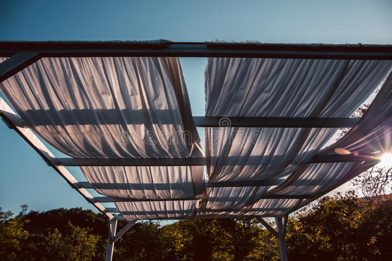 Gazebo de madera en la luz de oro de la hora, casi puesta del sol: paños blancos, luz suave, humor del verano, vacaciones, día de imagen de archivo