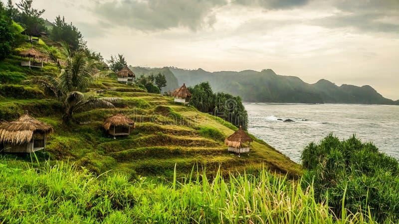 Gazebo lub buda w wierzchołku wzgórze blisko brzeg Tradycyjny dom w Menganti plaży, Kebumen, Środkowy Jawa, Indonezja fotografia stock