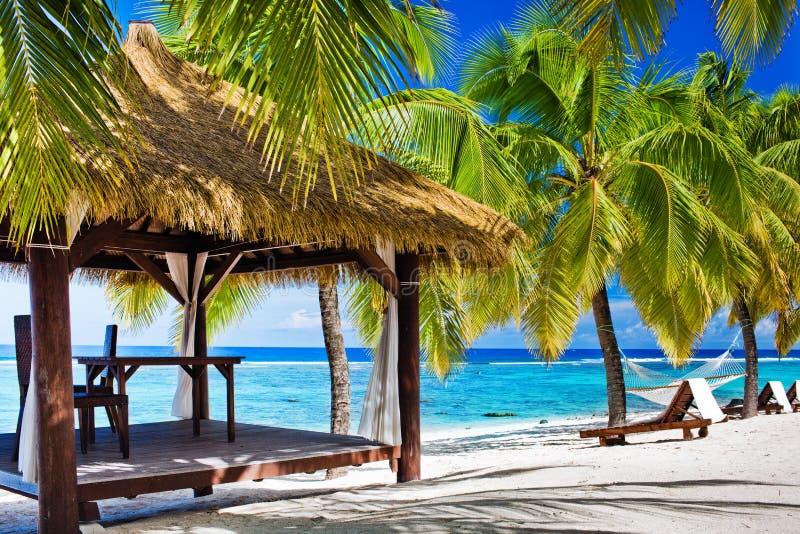 Gazebo met stoelen op verlaten strand met palmen royalty-vrije stock foto