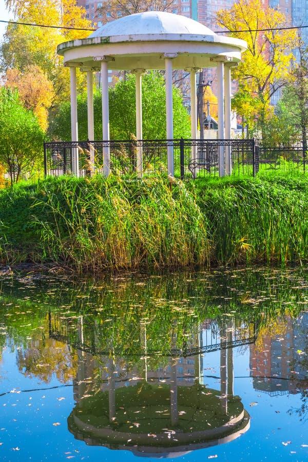 Gazebo nel parco e la sua riflessione in acqua fotografia stock libera da diritti