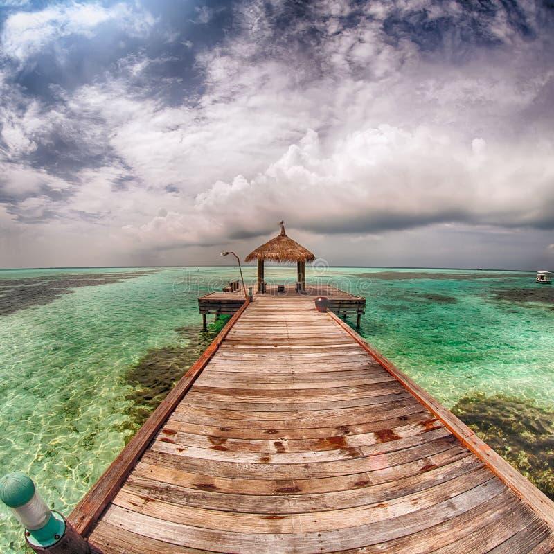 Gazebo z dachu pokrywającymi strzechą stojakami na jetty pod obłocznym niebem fotografia royalty free