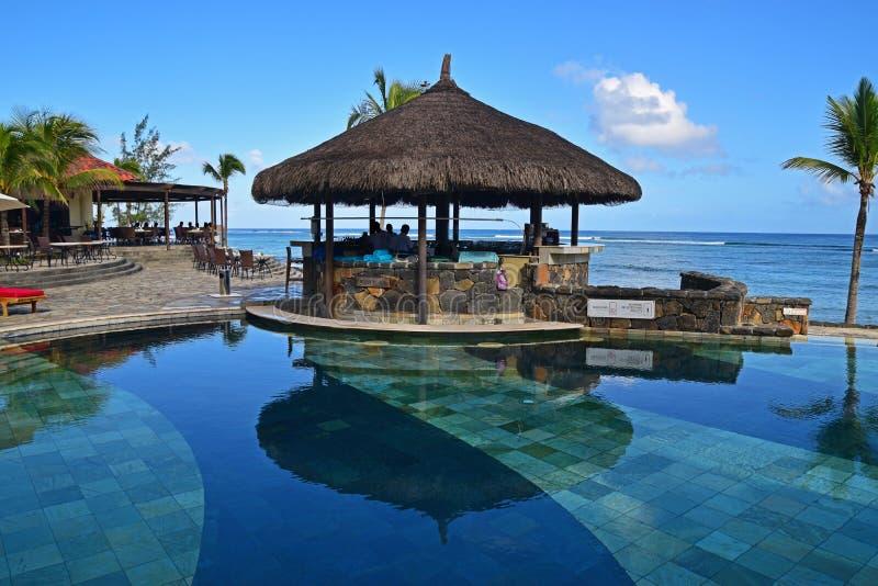 Gazebostång bredvid en pöl på den tropiska stranden av en hotellsemesterort arkivbilder