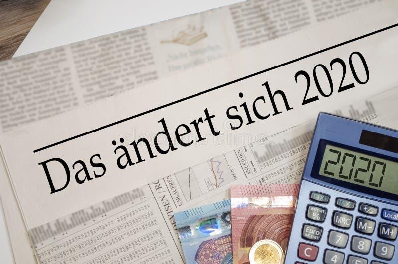 Gazeta z pieniędzmi, kalkulatorem i nagłówkiem w języku niemieckim Zmiany w roku 2020 - das ändert sich 2020 zdjęcia stock