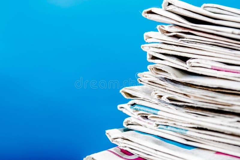 Gazety składać i brogować na stole z błękitnym tłem Zbliżenie sterty gazety i selekcyjnej ostrości wizerunek Czas czytać przeciw zdjęcia stock