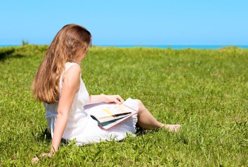 gazon czyta siedzi studenckiego podręcznika zdjęcia stock