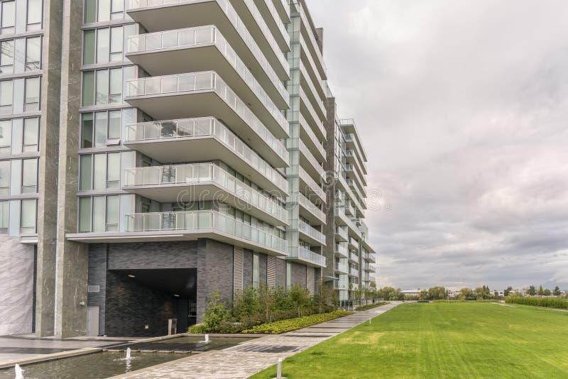 Gazon met gras dichtbij een nieuwe moderne residenti wordt behandeld die met meerdere verdiepingen stock afbeeldingen