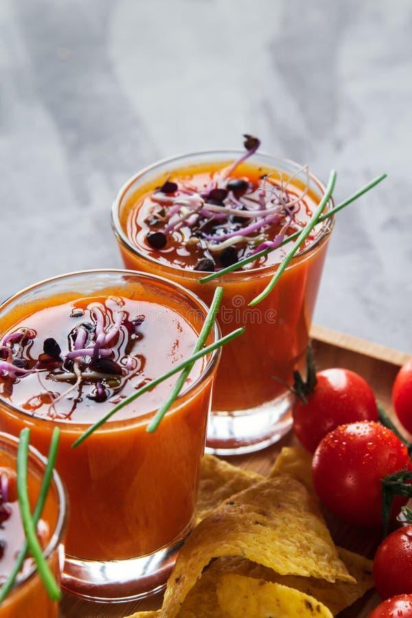 Gazpacho da sopa do tomate nos vidros com os brotos brotados acompanhados com as microplaquetas de milho em claro - fundo cinzent imagens de stock