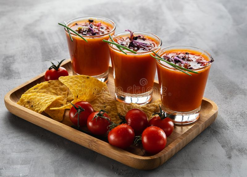 Gazpacho da sopa do tomate nos vidros com os brotos brotados acompanhados com as microplaquetas de milho em claro - fundo cinzent fotografia de stock royalty free