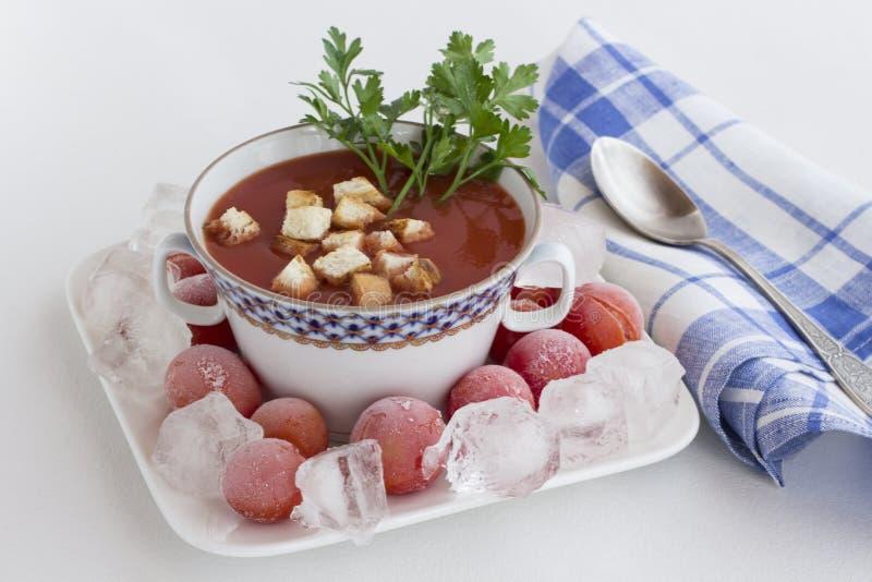 Gazpacho, soupe de tomate froide d'été Glace et tomates surgelées dans une assiette Papier à carreaux bleu, fond blanc photo libre de droits