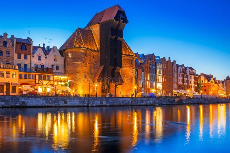 Gdansk bij nacht met historische die havenkraan in Motlawa ri wordt weerspiegeld stock afbeeldingen