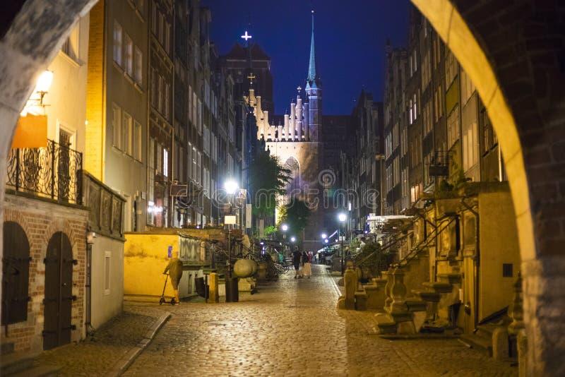 Gdansk old town street in evening. Nice empty of tourists Gdansk old town street with catholic church in dark blue sky royalty free stock photos