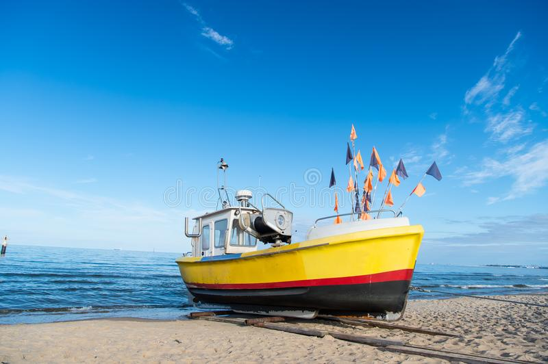 Boat on sand beach in Gdansk, Poland. Small ship on sea shore on blue sky. Vessel and water transport. Summer vacation stock photography