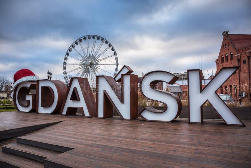 Gdansk, Polen - 15 december 2019: Stadsbord van Gdansk bij het ferris-wiel met kersthoed, Polen stock afbeeldingen