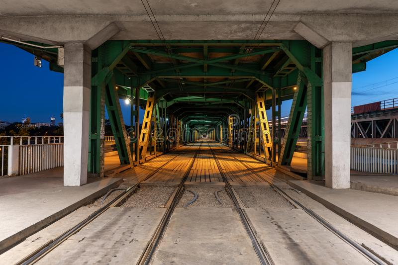 Gdanski Bridge by Night in Warsaw. Gdanski Bridge at night in city of Warsaw, Poland, illuminated steel, concrete and wood construction with tramway rails, urban royalty free stock images