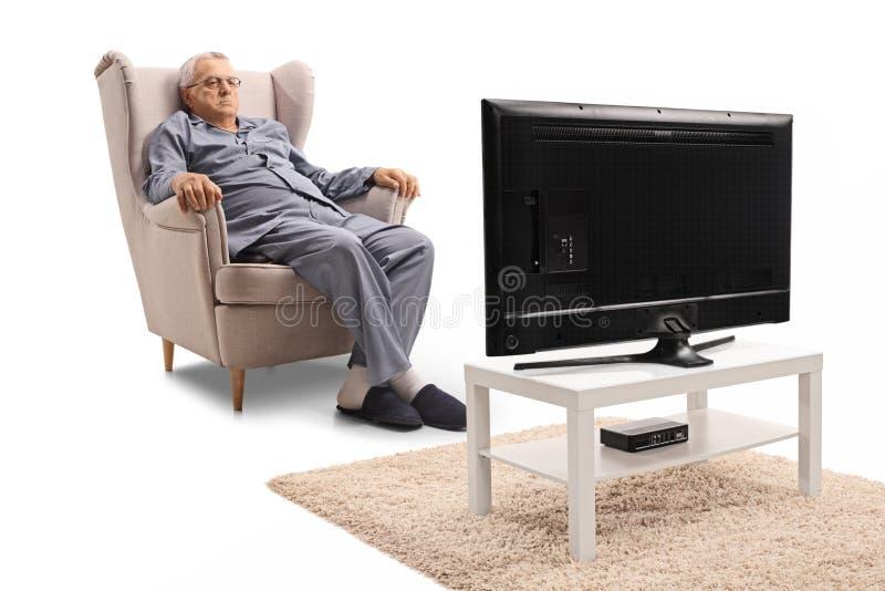 Gderliwy dorośleć mężczyzna siedzi w oglądać i karle w piżamach obrazy royalty free