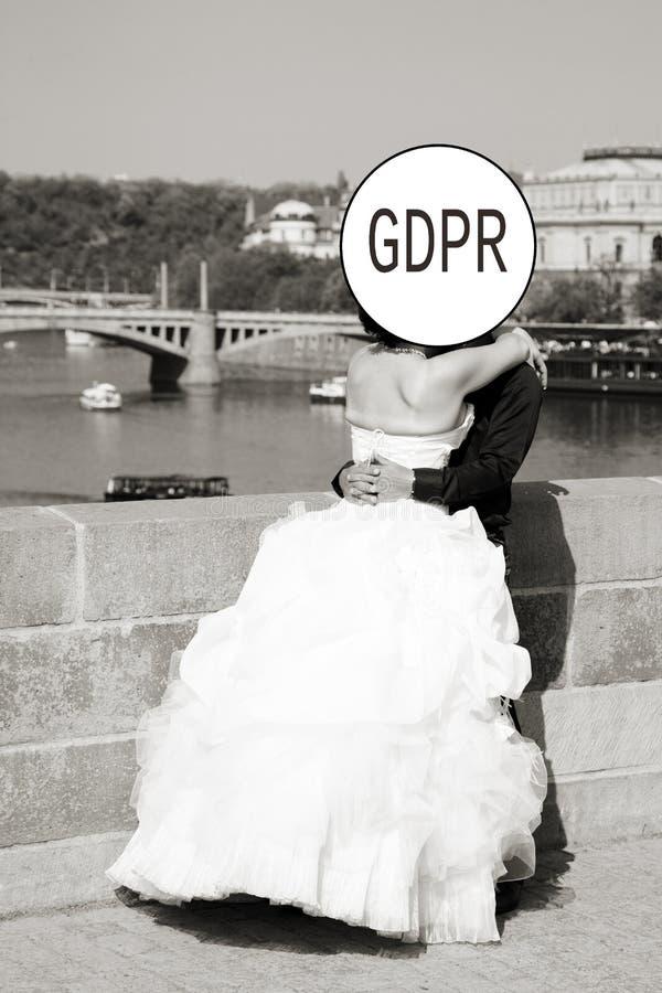 GDPR - выхольте и невеста в великолепном белом платье целует, их стороны спрятана данными по надписи общими стоковое изображение