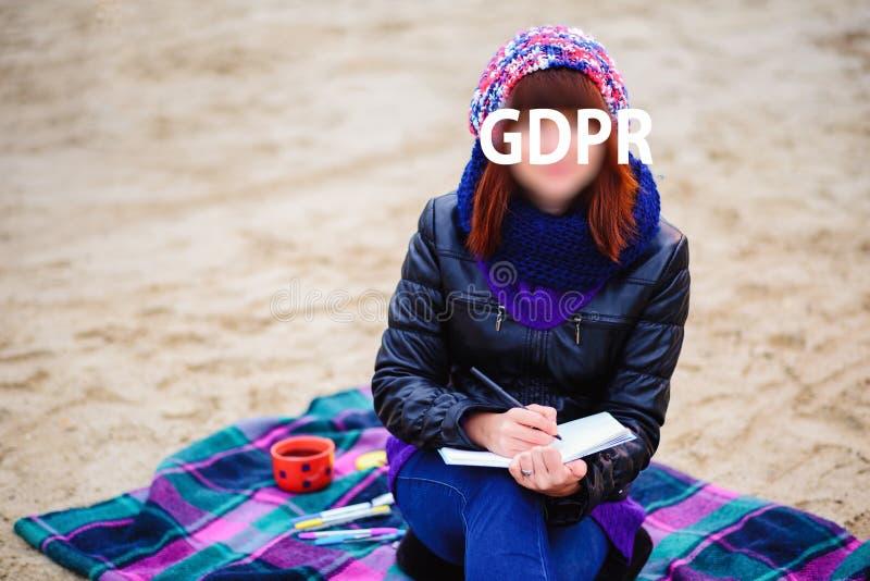 Gdpr, bella ragazza che si siede sulla spiaggia e che fa alcune note o che scrive nel taccuino o nel diario fotografia stock libera da diritti