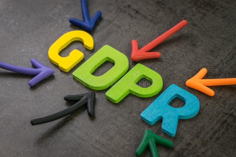 GDPR, conceito regulamentar da proteção de dados geral, setas coloridas que apontam à palavra GDPR no centro do cimento preto fotos de stock