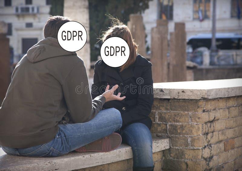 GDPR - ein junges Paar hat ein angespanntes Gespräch, ihre Gesichter werden versteckt durch die Schutz-Regelung Aufschrift Genera lizenzfreie stockfotografie