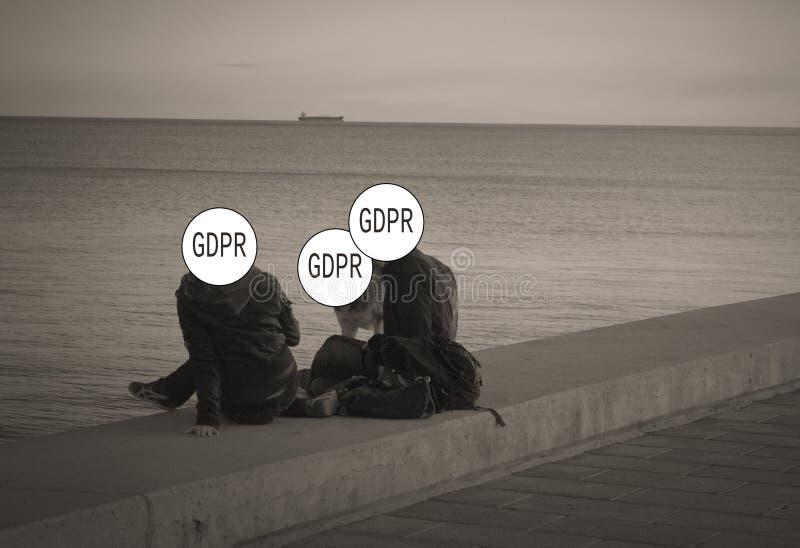 GDPR - ein junges Paar mit einem Hund, der auf dem Strand, ihre Gesichter spricht, werden hinter dem Schutz Aufschrift General-Da lizenzfreie stockfotos