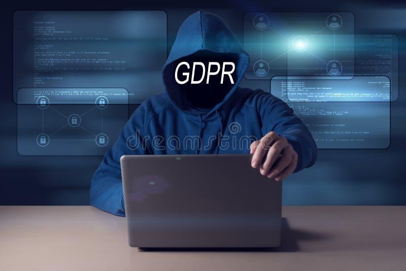GDPR En hacker som döljer hans framsida bak en reglering för skydd för allmänna data för inskrift arkivfoton