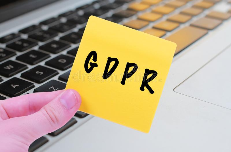 GDPR EU General Data Protection Regulation in Europe on a sticky note being held by a hand in front of laptop computer. GDPR EU General Data Protection stock photography