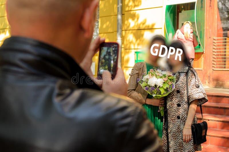 Gdpr gör jag ett foto på en mobiltelefon av två kvinnor, som kramar och en för dem som rymmer en bukett av blommor, vänder mot co arkivbild