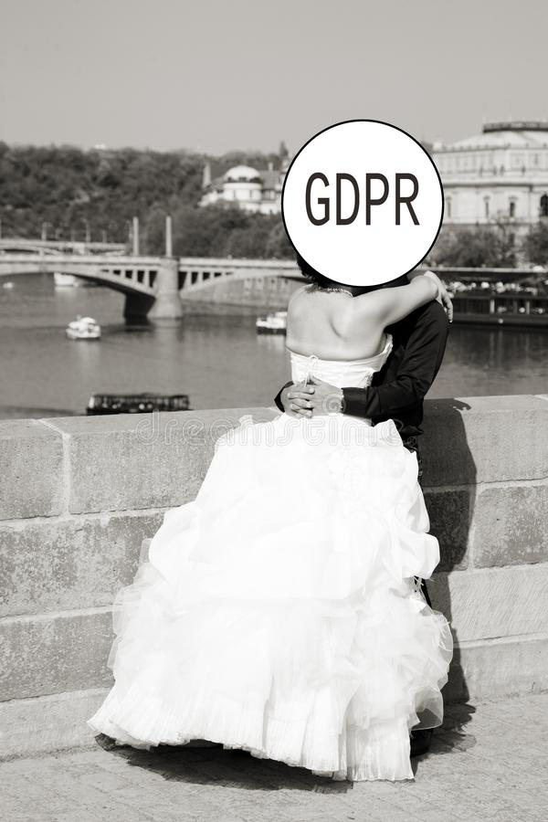 GDPR - the groom and the bride in a magnificent white dress are kissing, their faces are hidden by the inscription General Data. Protection Regulation. Cyber stock image