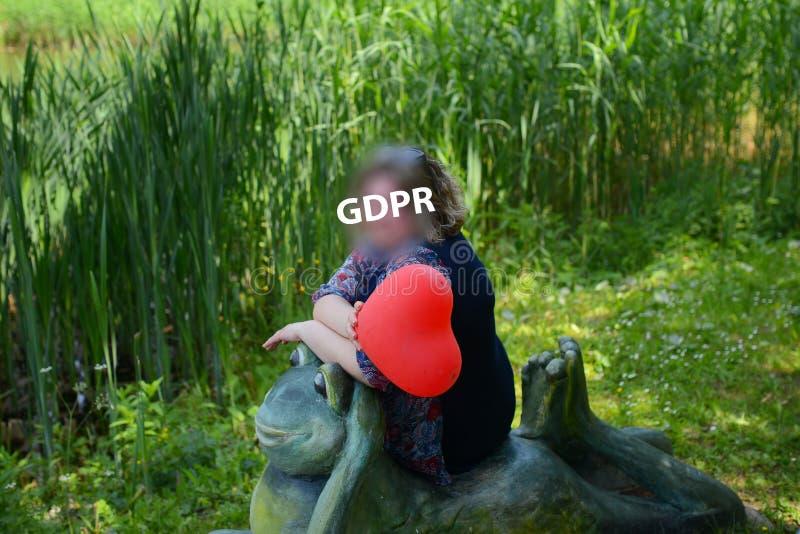 Gdpr, portrait d'une femme plus âgée au jardin vert, elle tient le ballon en forme de coeur et s'assied sur la sculpture en a d'u photographie stock