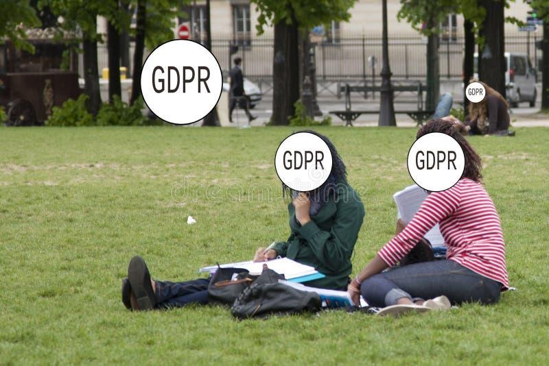 GDPR - zwei Mädchen sitzen auf dem Gras im Park, ihre Gesichter werden versteckt durch den Schutz Aufschrift General-Daten lizenzfreie stockfotografie