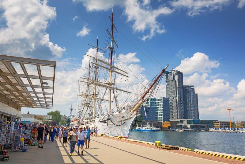 Gdynia, Polônia - 8 de junho de 2019: Fragata polonesa Dar Pomorza no Mar Báltico com arranha-céus das Torres do Mar em Gdynia imagem de stock