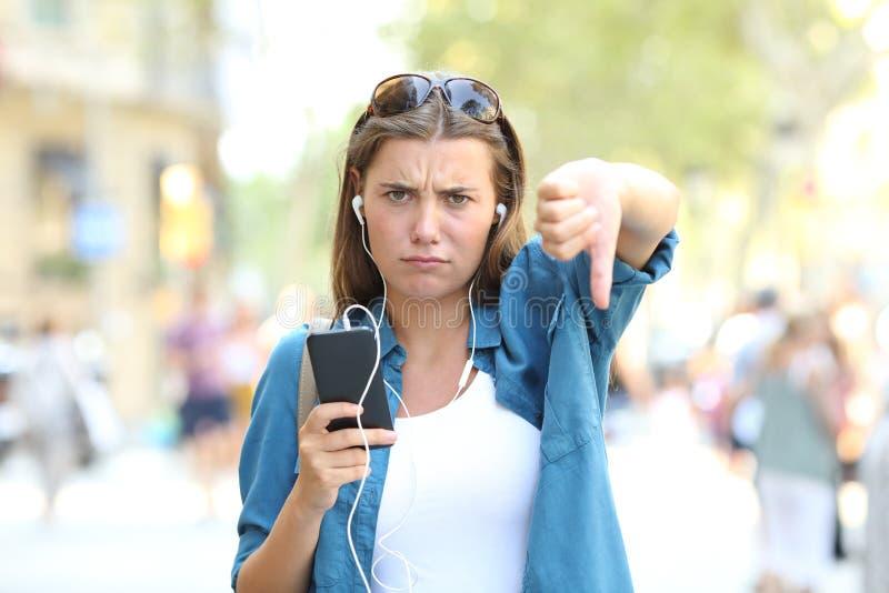 Geërgerd meisje die aan muziek met neer duimen luisteren royalty-vrije stock foto's