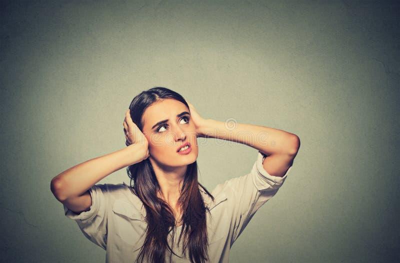 Geërgerde beklemtoonde vrouw die haar oren behandelen, die omhoog hevig lawaai kijken stock afbeelding