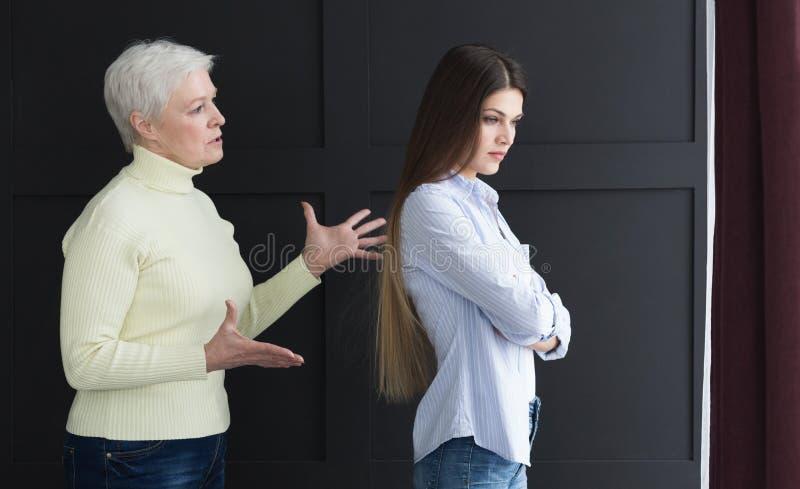 Geërgerde dochter die met hogere moeder debatteren, die haar negeren stock foto