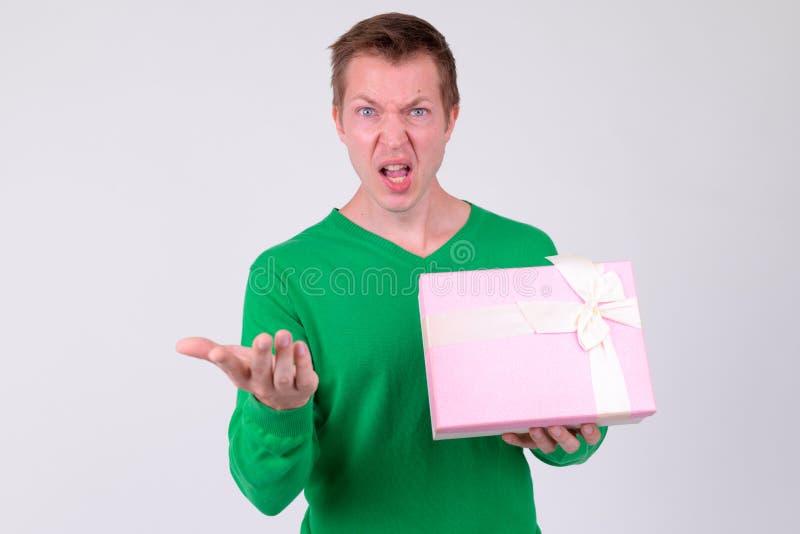 Geërgerde jonge mens met giftdoos klaar voor de dag van Valentine royalty-vrije stock foto
