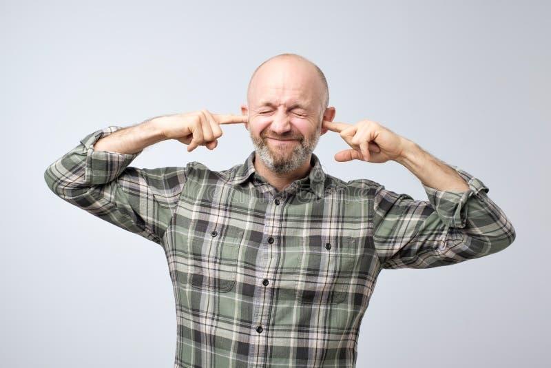 Geërgerde rijpe mens die oren met vingers stoppen stock foto